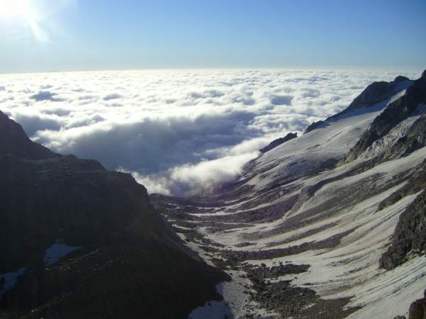 A gorgeous day in the Alps: at Zwischbergen pass 3268 m, above the clouds. Swiss Alps.